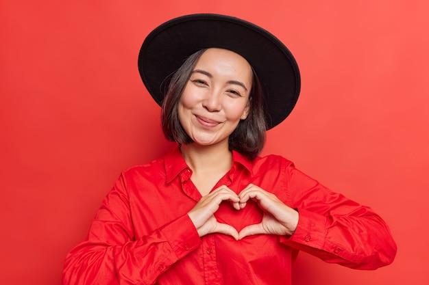 女性は胸の近くにハートのサインを示しています私はあなたを愛していますジェスチャーは鮮やかな赤に黒い帽子とシャツのポーズを着ています