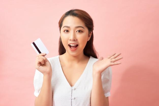 女性は彼女のクレジットカード、アジアの美しさを示しています