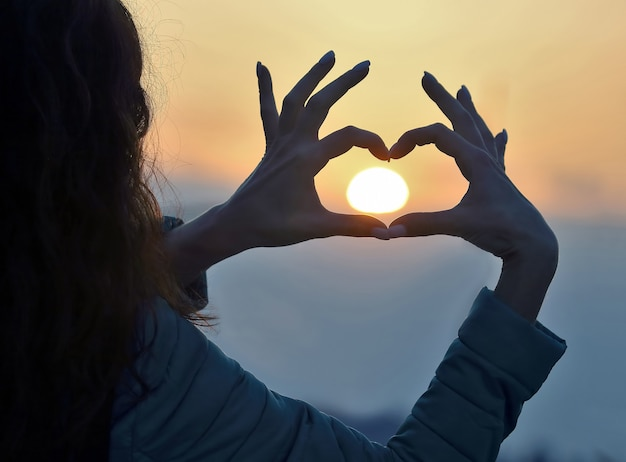 The woman shows her hands the sign of the heart against the setting sun