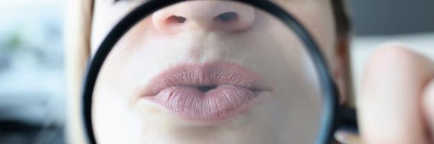 여자는 돋보기 입술 확대 추세 개념을 통해 그녀의 입술을 보여줍니다