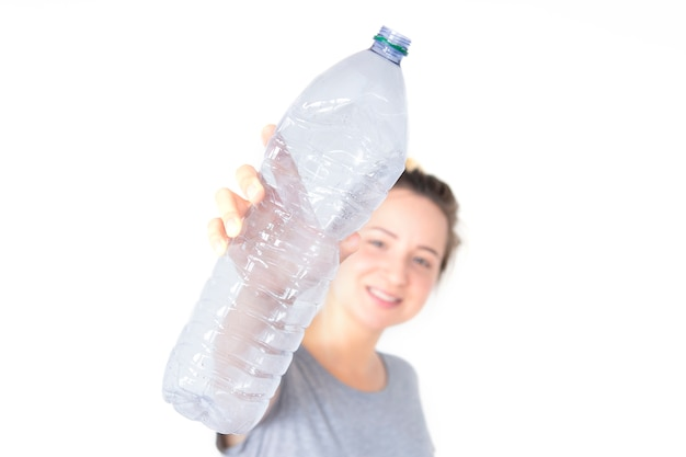 Woman shows and holding recyclable plastic bottle isolated on white background. waste separate collection.