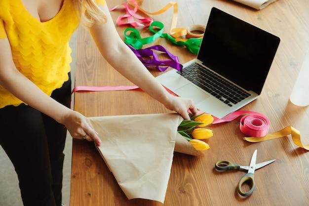 女性がチューリップで花束を作る方法を示しています