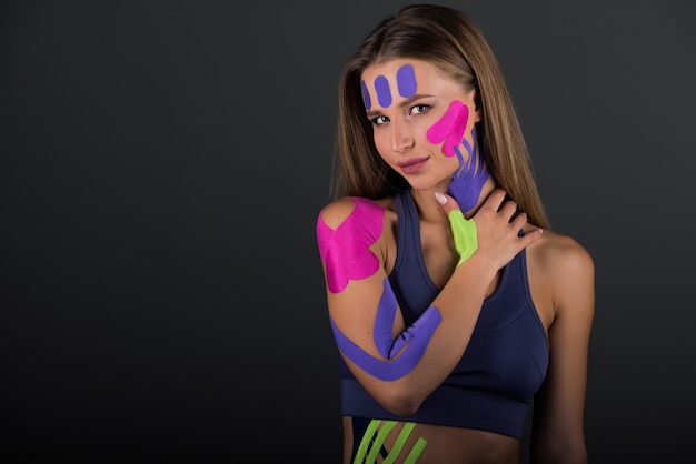 女性は彼女の腹にテープで留められたキネシオテープを示しています。腹部と脚に明るい医療用テープ