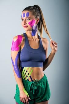 女性は彼女の体にテープで留められたキネシオテープを示しています