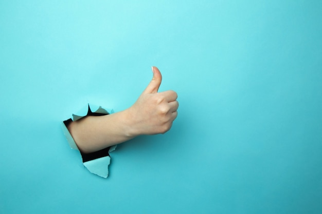 Woman shows like gesture through torn blue wall, keeps thumb up, says you are best, demonstrates approval sign, recommends something. copy space aside for your advertising content