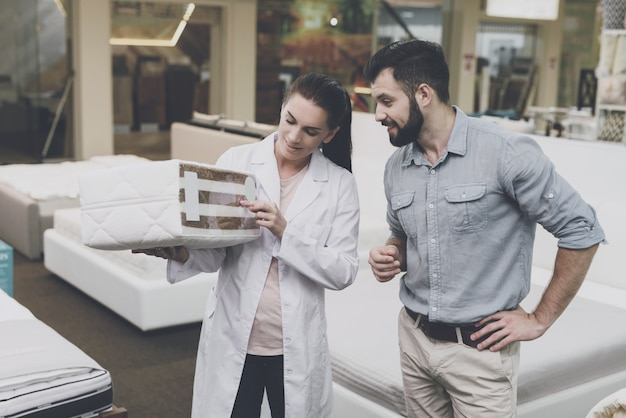 A woman shows a man a sample of a mattress.
