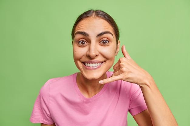 여자는 휴대 전화 제스처를 보여줍니다 전화 번호를 묻는 기호는 녹색에 캐주얼 핑크 티셔츠를 입고 기쁘게 생각합니다