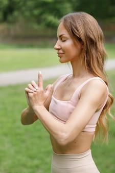Женщина показывает мудру руками крупным планом, вид сбоку