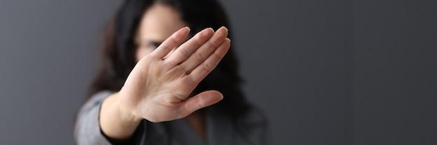 여자는 나쁜 습관 개념을 종료하는 그녀의 손으로 부정적인 제스처를 보여줍니다