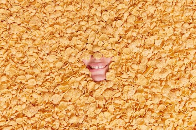 Woman shows only mouth bites lips shows white teeth going to eat delicious breakfast surrounded by dry cereals keeps to healthy diet drowned in cornflakes.