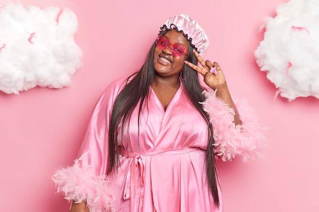 女性は目の上で平和のジェスチャーを示し、防水帽子をかぶり、ガウンはピンクのサングラスを通して室内を楽しみ、家で過ごす