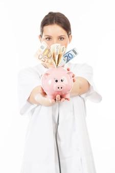 A woman shows a piggy bank full of european banknotes