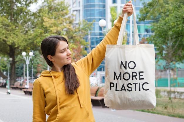 Женщина показывает многоразовую сумку с надписью без пластика