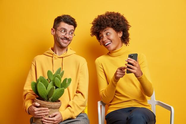 Женщина показывает парню что-то смешное на смартфоне, вместе проводят свободное время, сидя на стульях, изолированных на желтом