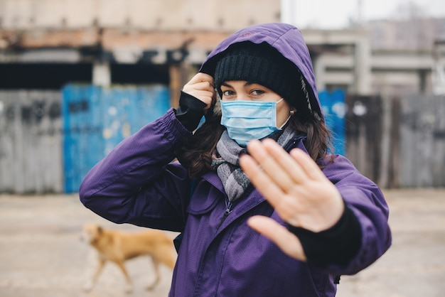 Woman shows stop with hands gesture for stop corona virus outbreak. wuhan coronavirus and epidemic virus symptoms. person in mask protection against. new coronavirus 2019-ncov from china.