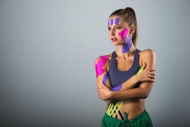 여자는 그녀의 몸에 테이프를 보여줍니다. 스포츠와 건강한 라이프 스타일 컨셉