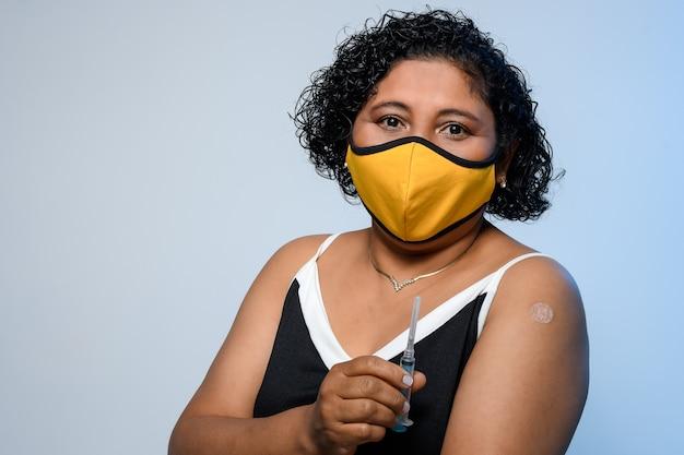 女性はワクチンcovid19を受け取った後、注射器とパッチを腕に見せます19