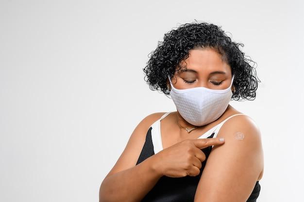 女性は彼女の腕にワクチンパッチを示しています。 covid-19