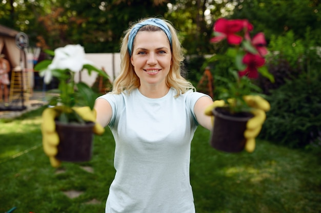 Woman shows two flowers in pots in the garden. female gardener takes care of plants outdoor, gardening hobby, florist lifestyle and leisure