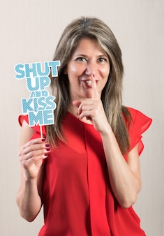 Woman in shushing gesture with photo booth prop