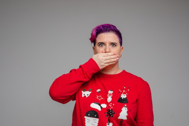 Женщина закрыла рот ладонью с потрясением на лице, сказав что-то, не подумав. новогодняя концепция