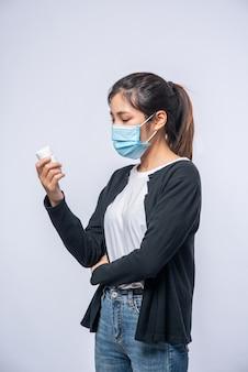 Una donna malata in piedi con una bottiglia di medicina