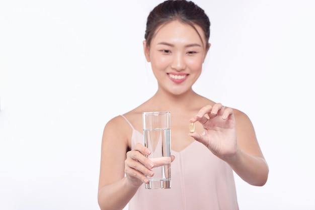 病気の女性、錠剤と水の入ったグラスを持つ女性