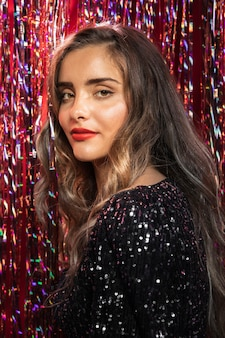Woman sideways standing in a curtain of sparkles