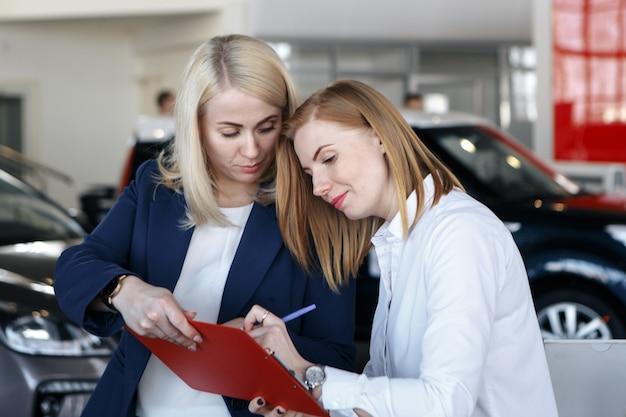 자동차 보험에 서명하는 여성, 에이전트가 문서를 가리키고 있습니다.