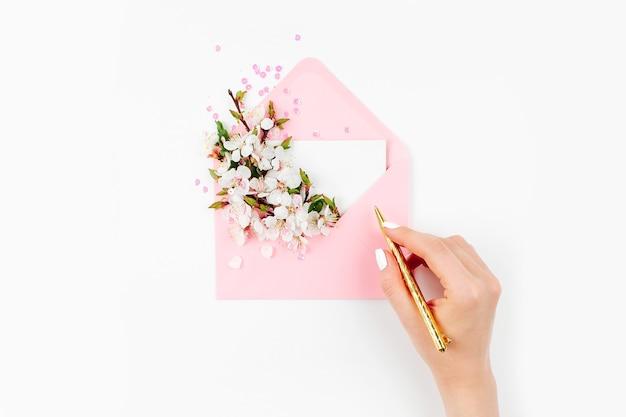 カードに署名する女性。空のカードと春のフラワーアレンジメントが入ったピンクの封筒。フラットレイ、上面図。