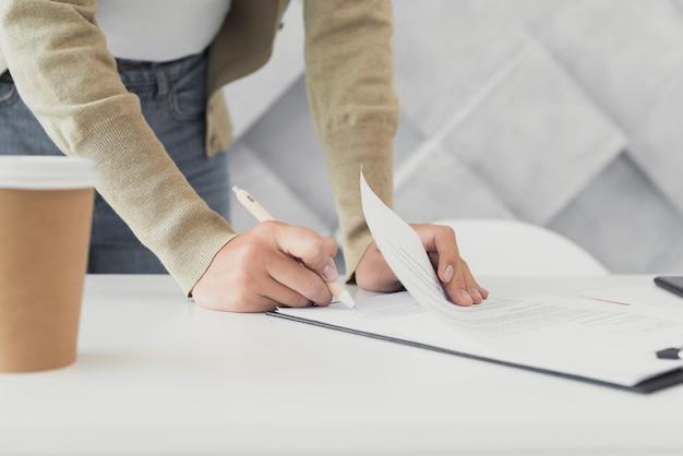 紙のクローズアップに署名する女性