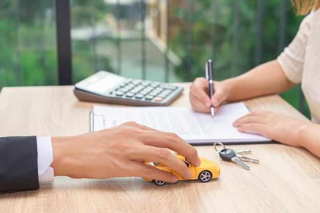 車の鍵と木製の机の電卓と車の貸し借契約書に署名する女性