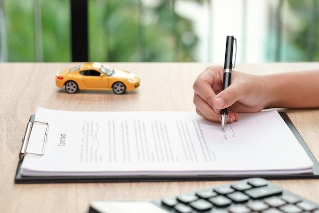 車のおもちゃと木製の机の上の電卓と契約している女性。