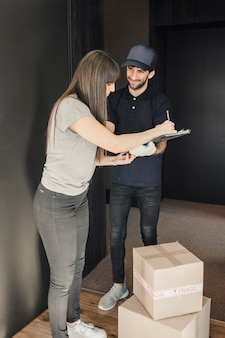 Woman signing on clipboard after parcel delivered by delivery man