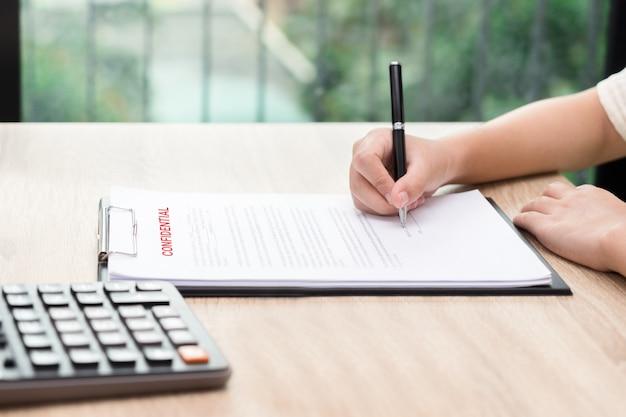 Woman signing on confidential contract with calculator on wooden desk.