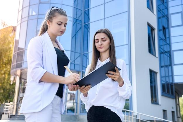 Женщина подписывает контракт в буфер обмена. они в деловых костюмах и стоят у офиса.