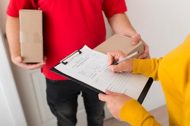 Donna che firma un documento di consegna