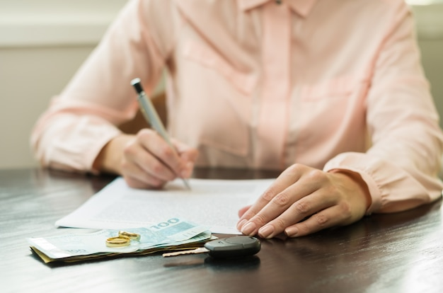 Woman signing divorce agreement with money, car key on the table