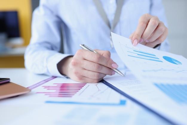 Женщина подписывает документ с графиками с крупным планом шариковой ручки