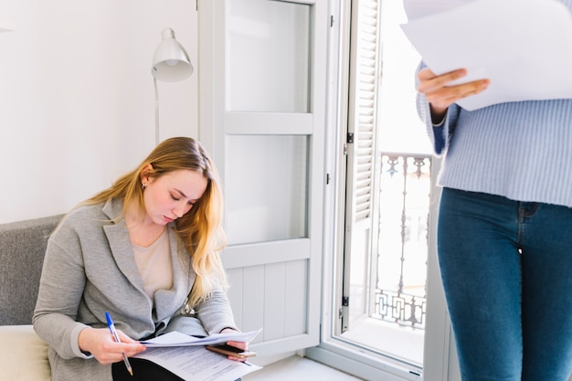 Woman signing documents in living room