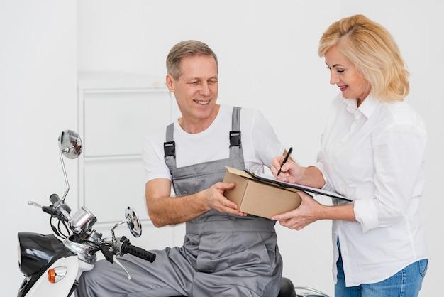 Женщина подписывает для доставки