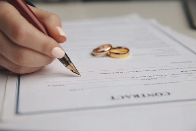 Woman signing marriage contract, closeup.