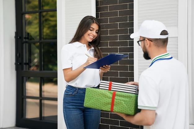 종이에 서명하고 상자를 받는 여성