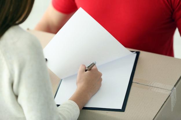 配達パッケージの領収書に署名する女性、クローズアップ