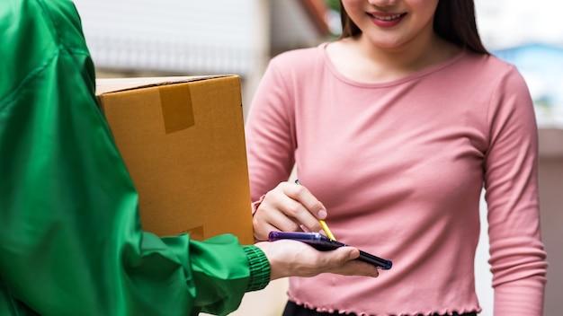 Подписание женщины получает цифровую подпись на смартфоне, чтобы принять коробку доставки