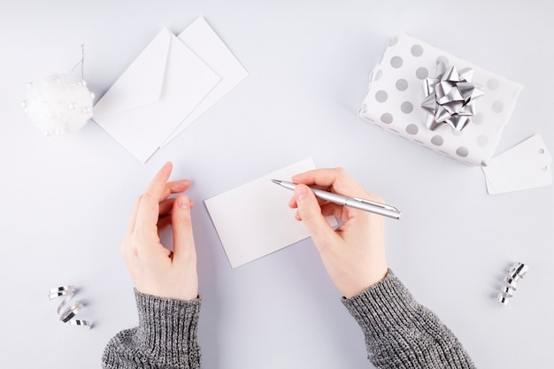 Woman signs card for gift in silver packaging, gray background. concept of preparation for holidays