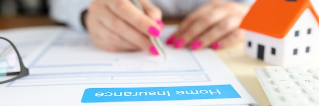 Woman signs documents of home insurance contract