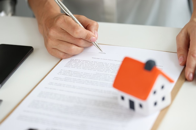 Woman signs home purchase agreement buying real estate with a loan or mortgage concept