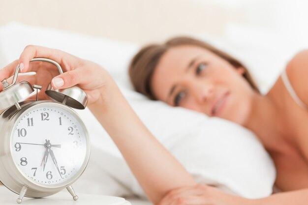 Женщина, заставляющая замолчать ее будильник, сосредоточиться на часах