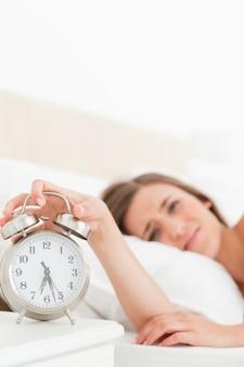 Женщина, запирающая ее будильник ее рукой